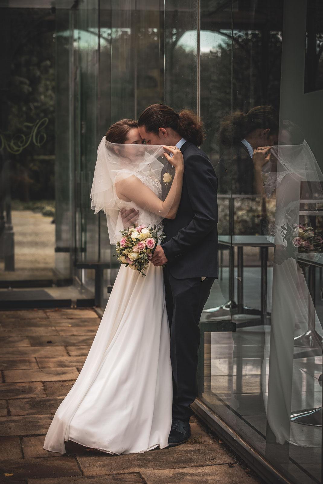 Brautpaar versteckt sich hinter dem Schleier