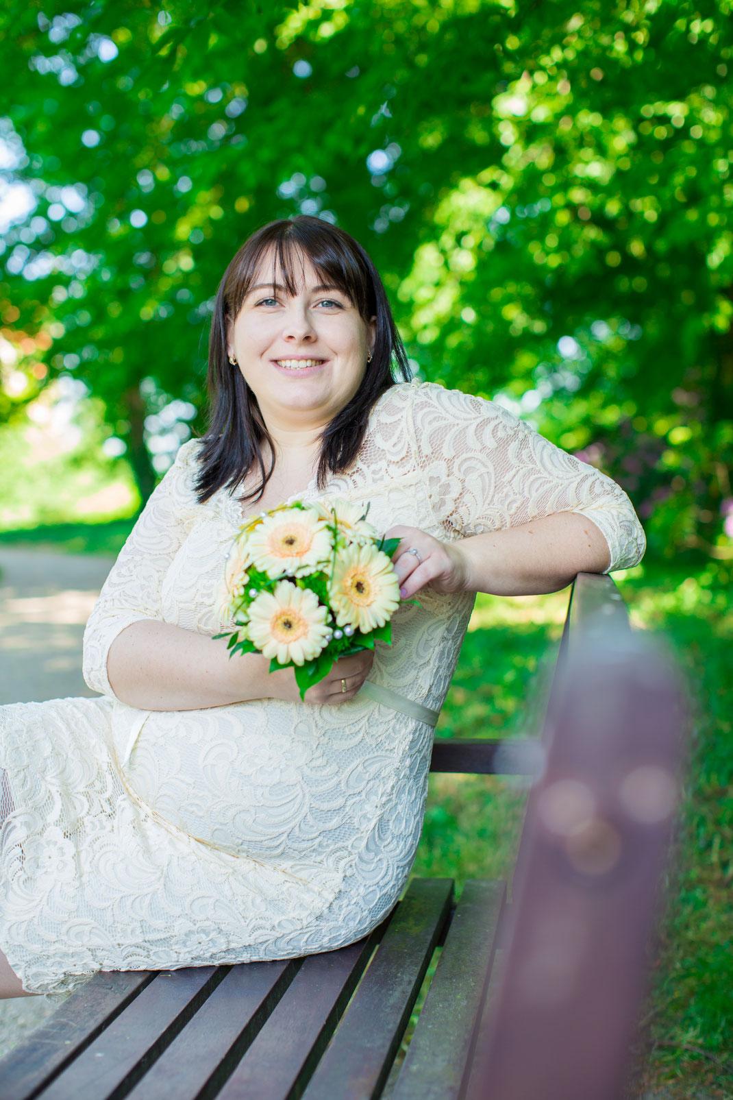 Die Braut ist vor dem Hochzeitsfotografen ziemlich locker und passiert auf der Bank