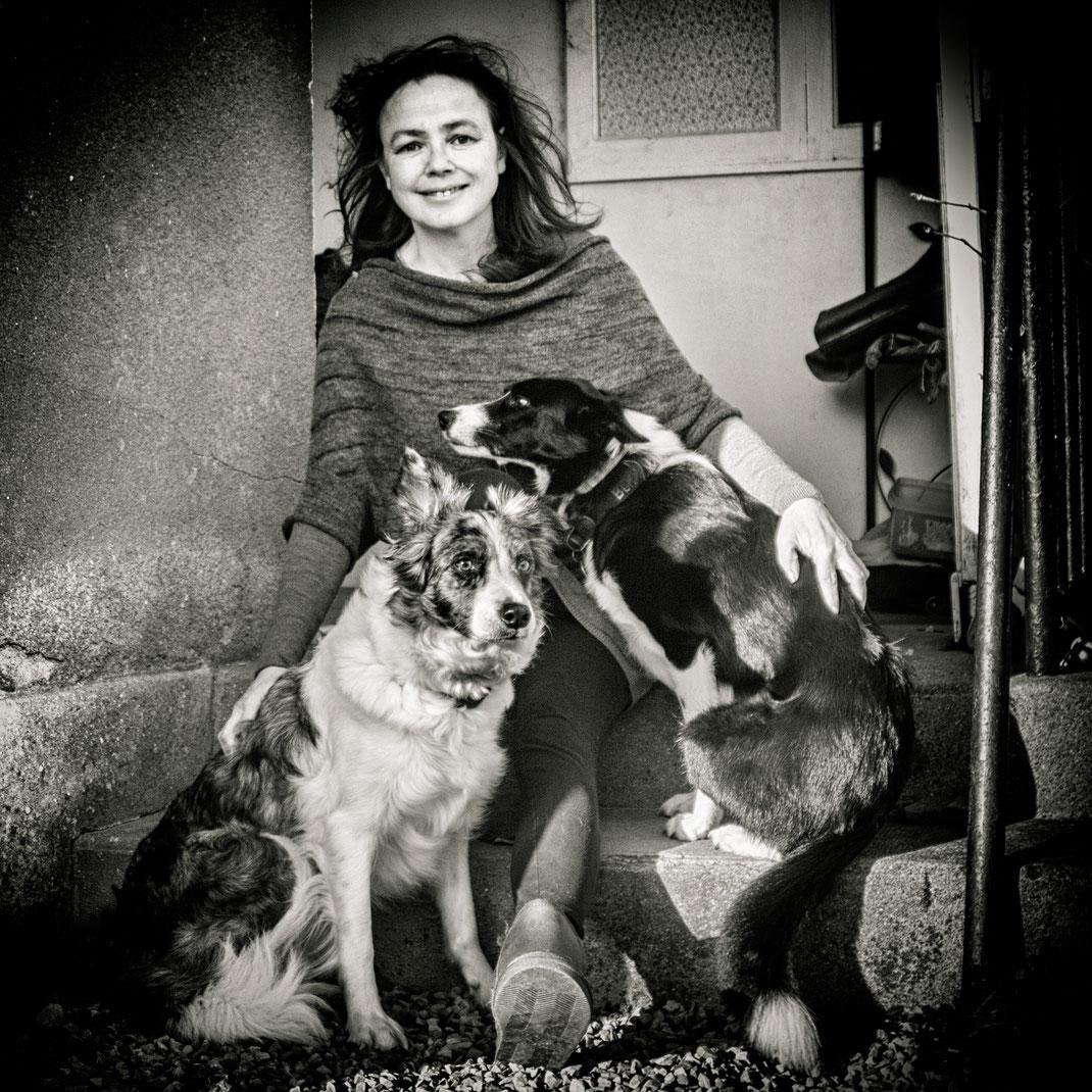 Barbara Homolka mit den Border Collies Idgie und Ben in einem Hauseingang