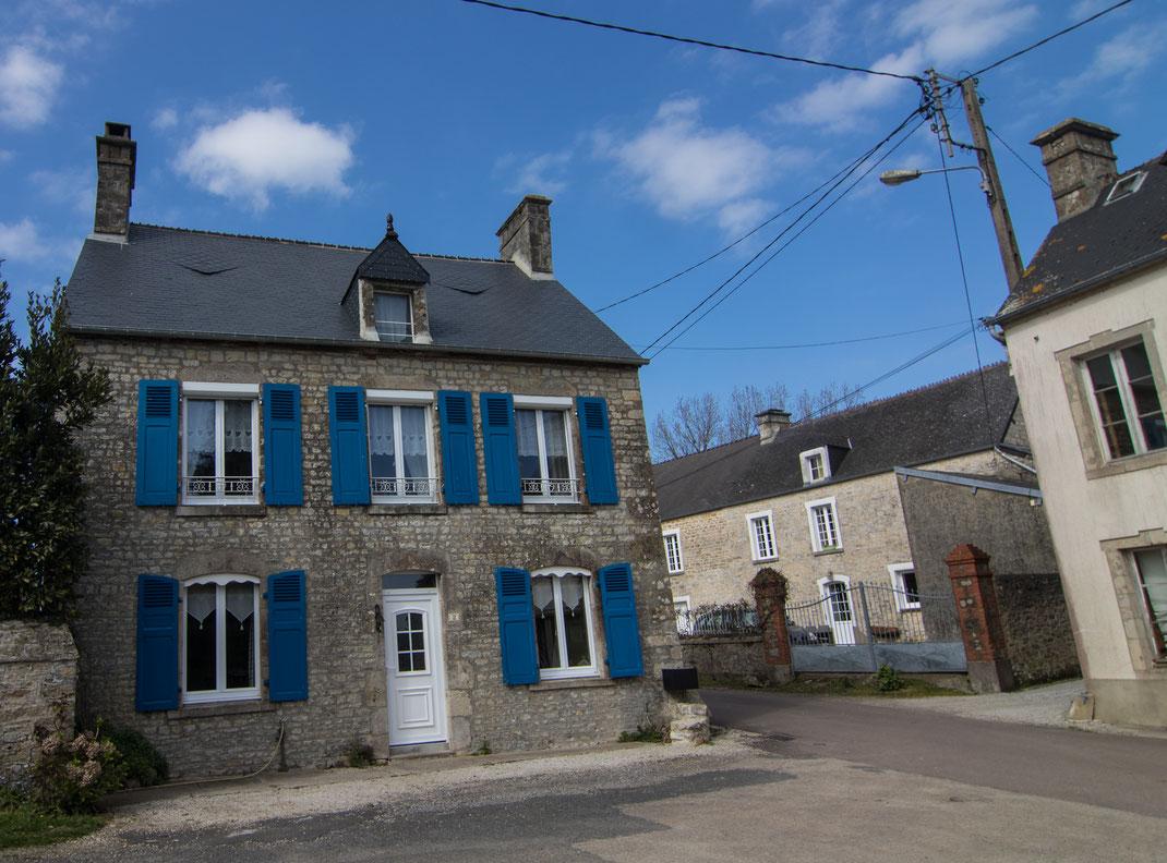 Ein Steinhaus auf der Halbinsel Cotentin in Fresville mit blauen Fensterläden