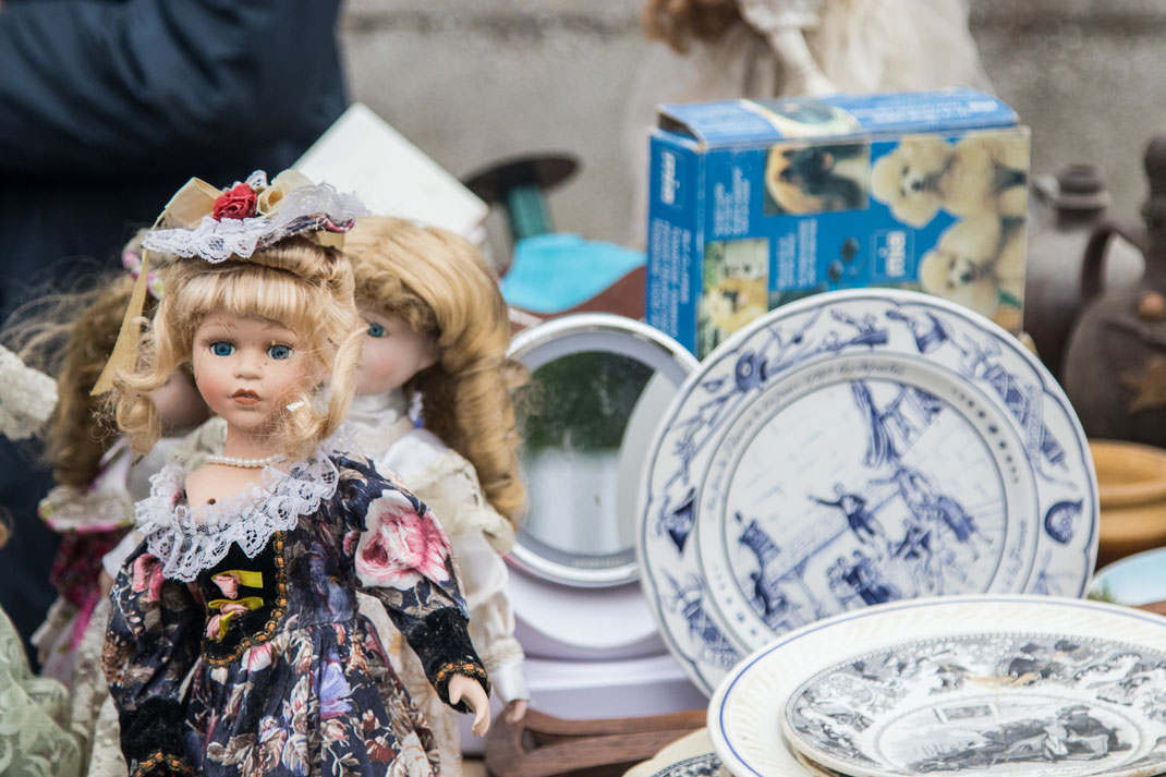 Puppen und Teller auf einem Flohmarktstand in Pirou in der Normandie
