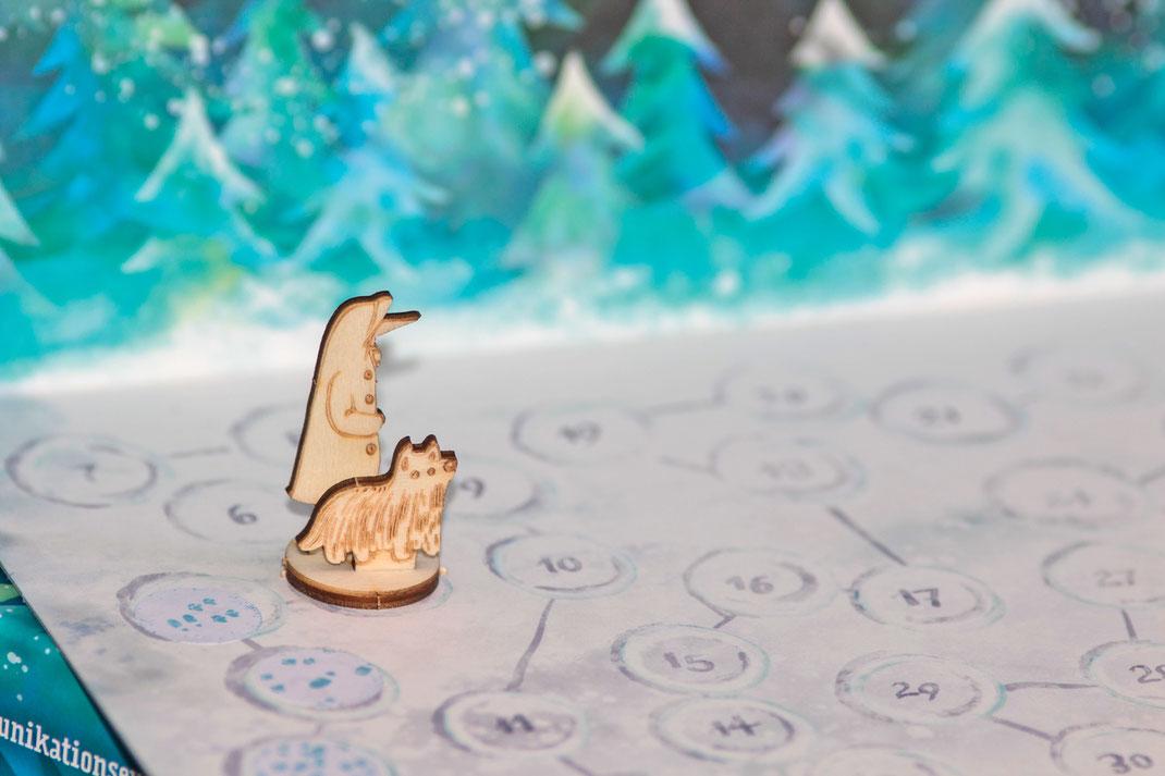 Zwei Holzspielfiguren stehen auf dem Spielplan zu Schnauzberts Winterreise.