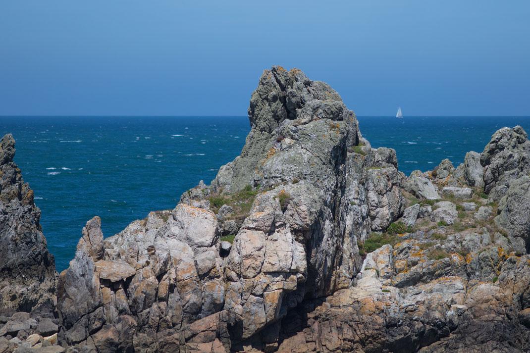 Felsformation am Cap de La Hague in der Normandie, am Horizont fährt ein Segelboot.