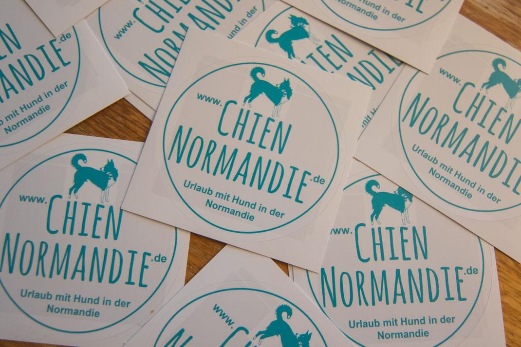 Aufkleber mit chienNormandie-Logo liegen auf einem Holztisch.