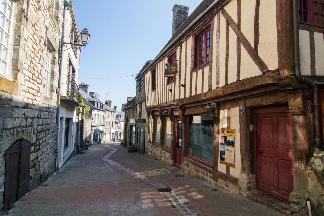 Fachwerk- und Steinhäuser in einer Gasse in Domfront/Orne in der Normandie
