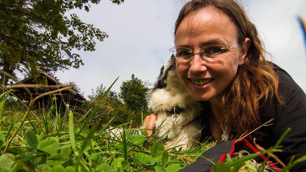 Frau mit Hund liegt im Gras