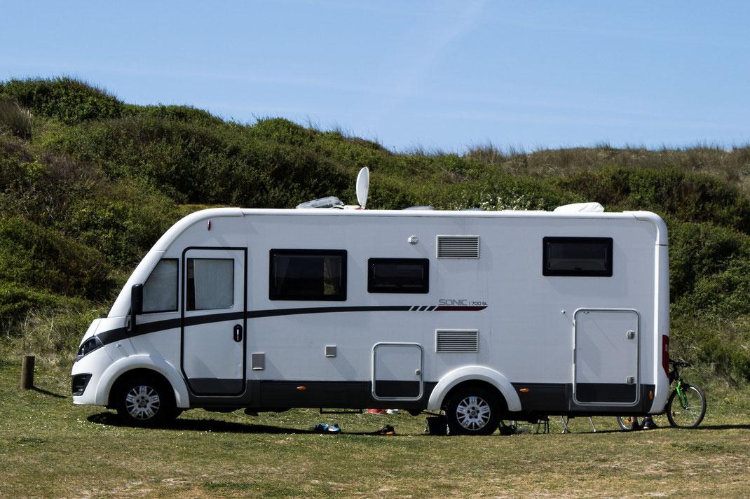 Ein Wohnmobil steht in den Dünen der Normandie.