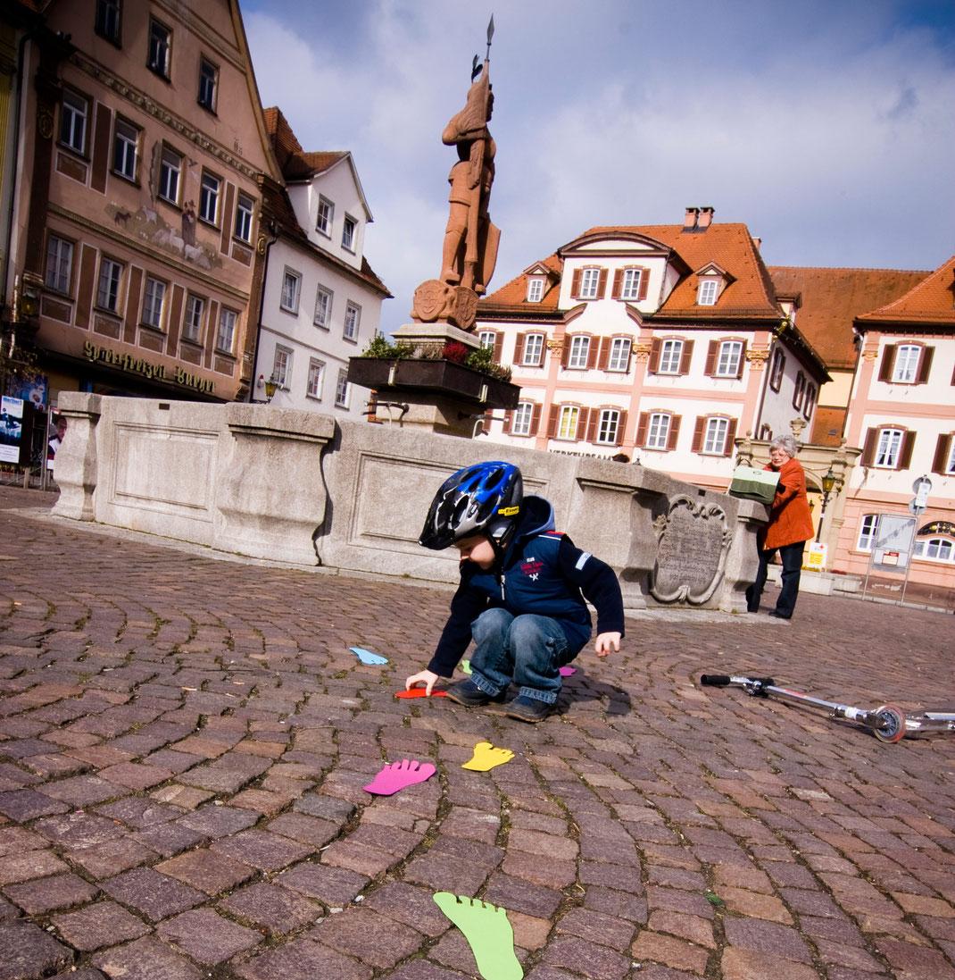 Ein Kind greift auf dem Marktplatz in Bad Mergentheim nach einer Fußspur aus Papier.
