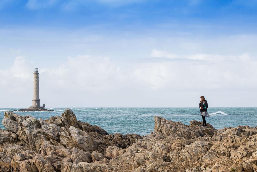 Eine junge Frau auf Felsen vor dem Leuchtturm Goury in der Normandie.