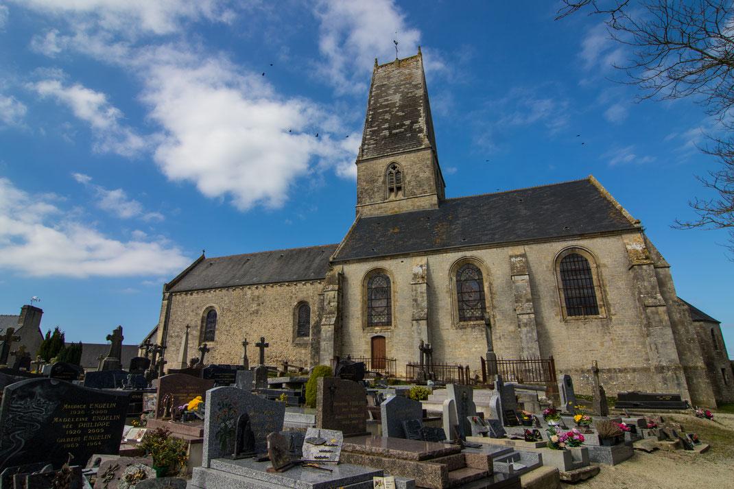 Eine alte normannische Kirche und der Friedhof in Fresville auf dem Cotentin.