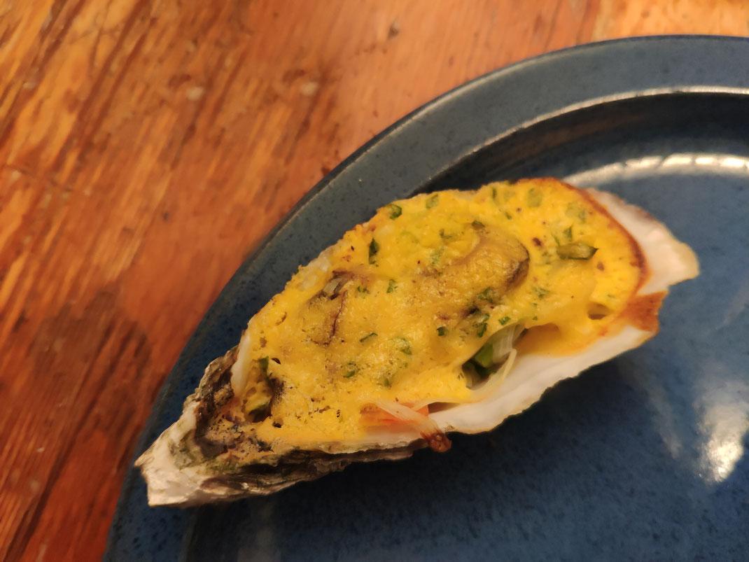 Eine überbackene Auster liegt auf einem blauen Teller