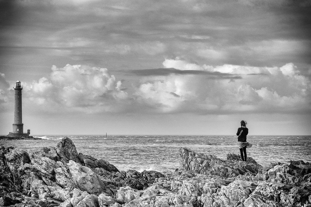 Eine Frau steht in den Felsen und schaut zum Leuchtturm in Goury in der Normandie.