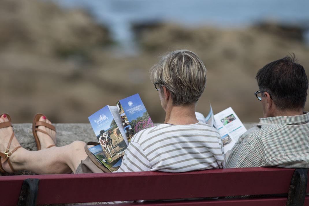 Ein Paar sitzt auf einer Bank in Barfleur in der Normandie und liest.