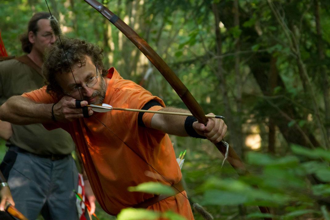 Ein Bogenschütze schießt mit einem Holzbogen im Wald