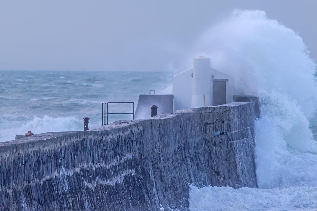 Eine Welle bricht auf der Kaimauer in Barneville-Carteret in der Normandie.