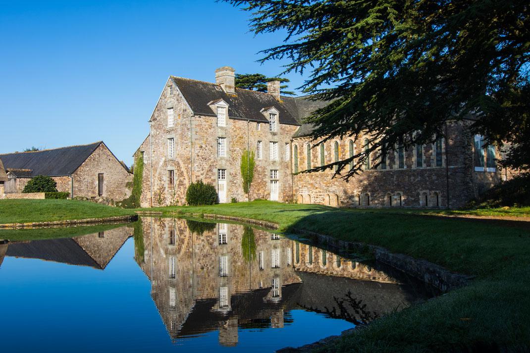 Ein Nebengebäude der Abbaye de la Lucerne in der Normandie spiegelt sich im ehemaligen Mühlensee