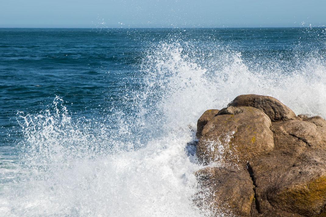 Eine Welle bricht sich am Fels beim Cap Levi auf der Cotentin-Halbinsel in der Normandie