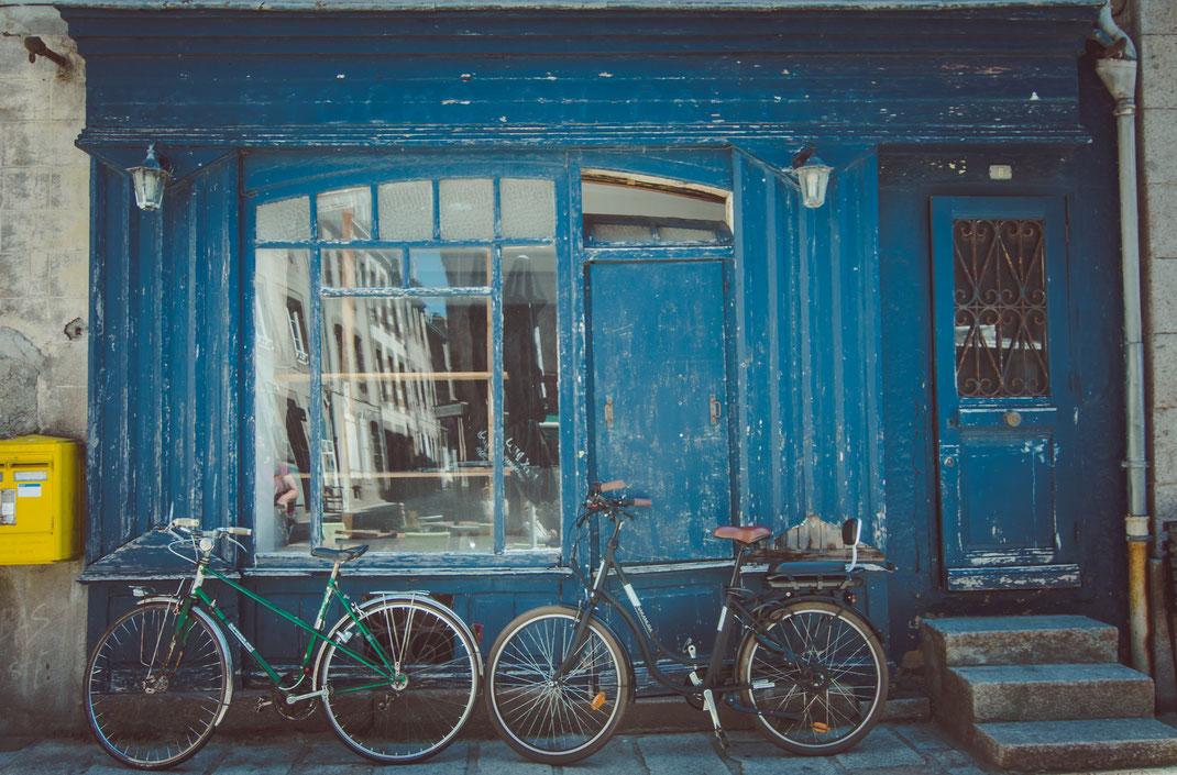 Zwei Fahrräder stehen vor einem maroden Schaufenster in Granville
