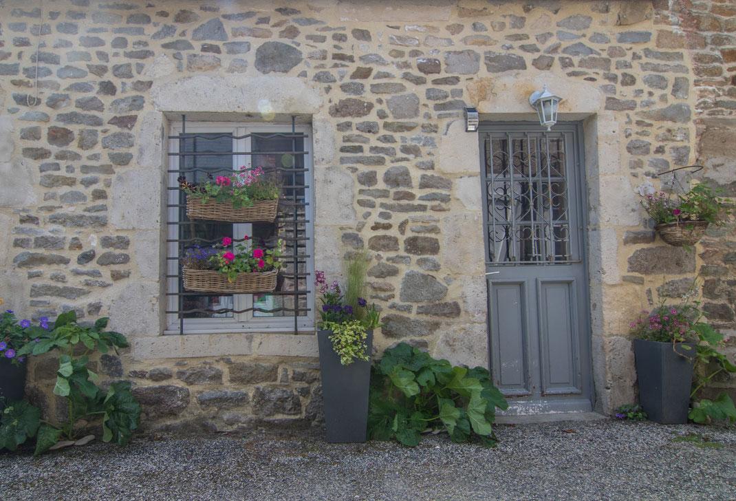 Tür, Fenster und Blumenschmuck eines Hauses in Saint-Vaastr-La-Hougue in der Normandie