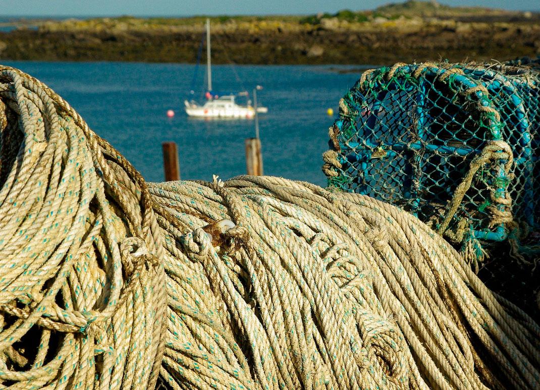 Seetaue und Hummerkörbe liegen auf den Chausey-Inseln in der Normandie, im Hintergrund ein Segelboot.