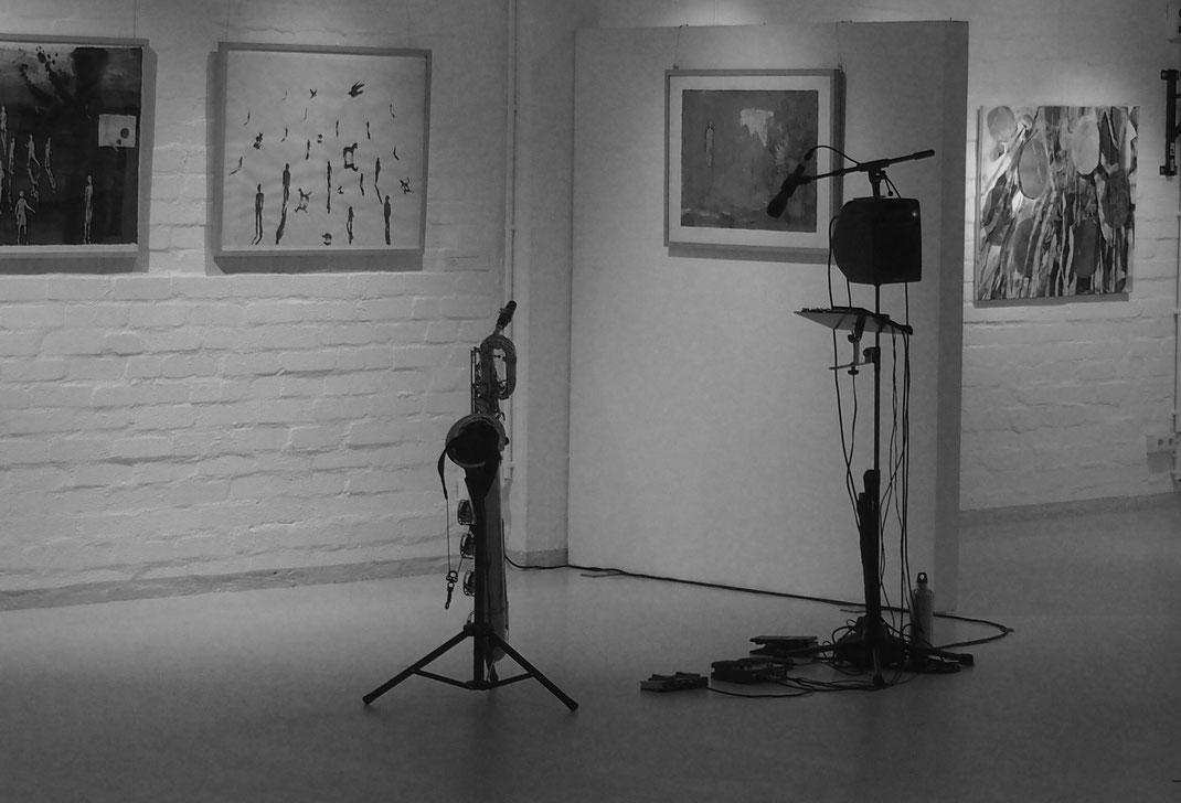 vor einer Bilderausstellung stehen das Bariton Saxofon und die Anlage für Live-Loops von Anne Wiemann, sie ist noch nicht auf der Bühne