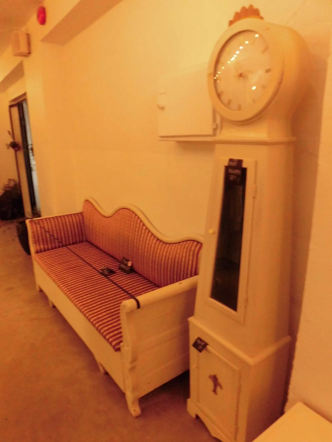 通路に置いてあったアンティークな時計とソファ、珍しいデザインだ
