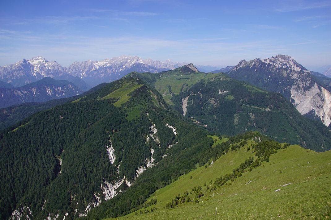 Der Blick nach Südwesten schweift von den Julischen zum Mittagskogel, im Vordergrund der Hahnkogel und als markante kleine Spitze rechts der Bildmitte der Große Frauenkogel
