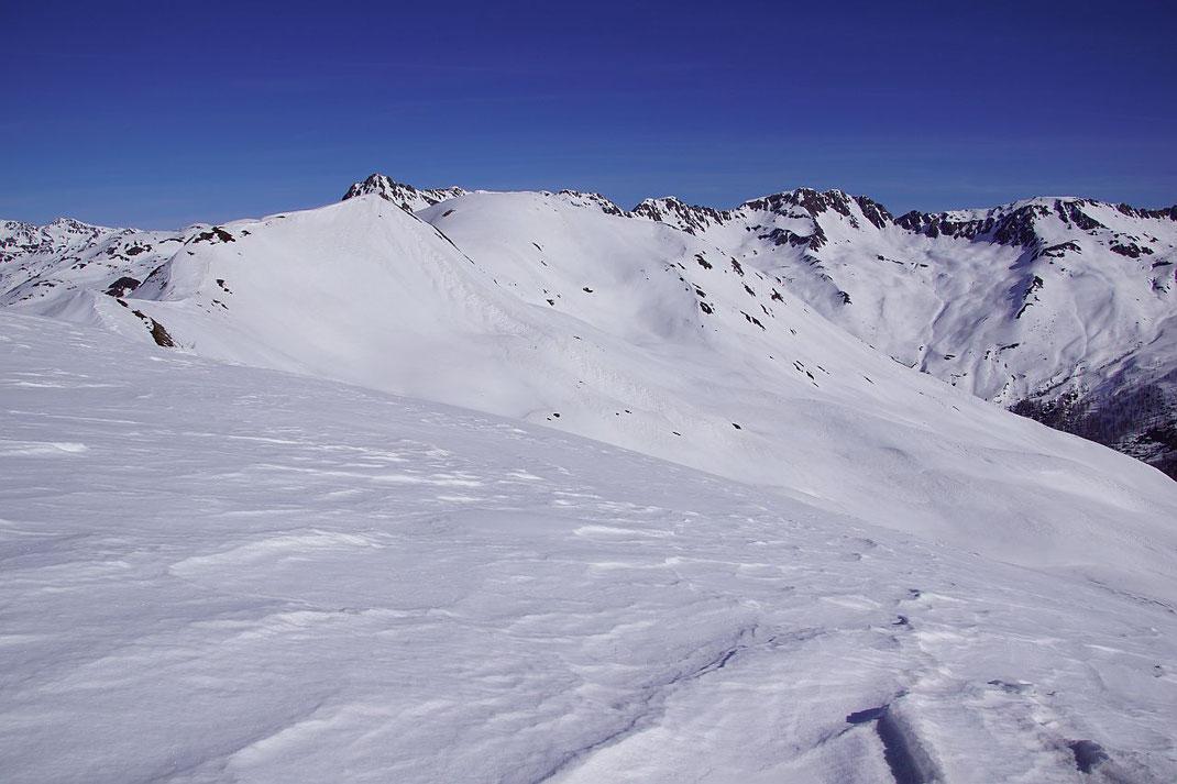 Vom 2242m hohen Gipfel der Blick zum Putzen (breiter weießer Rücken in der Bildmitte). Die Abfahrt erfolgt durch die herrliche Mulde zu den flachen Hängen rechts der Bildmitte.