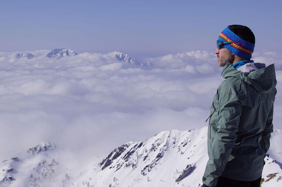 Nur die höchsten Gipfel der Karnischen Voralpen ragen aus der hochnebelartigen Bewölkung auf der italischen Seite heraus.