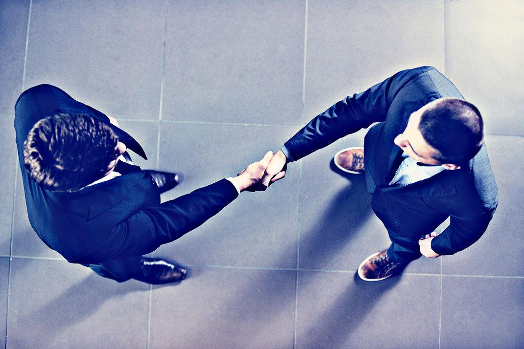 Zwei Männer geben sich die Hand als Zeichen eines abgeschlossenen Handels