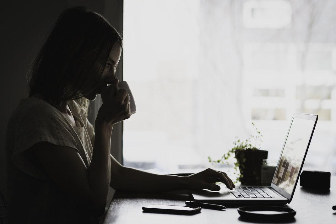 女性がパソコンを使いながら飲み物を飲んでいる画像