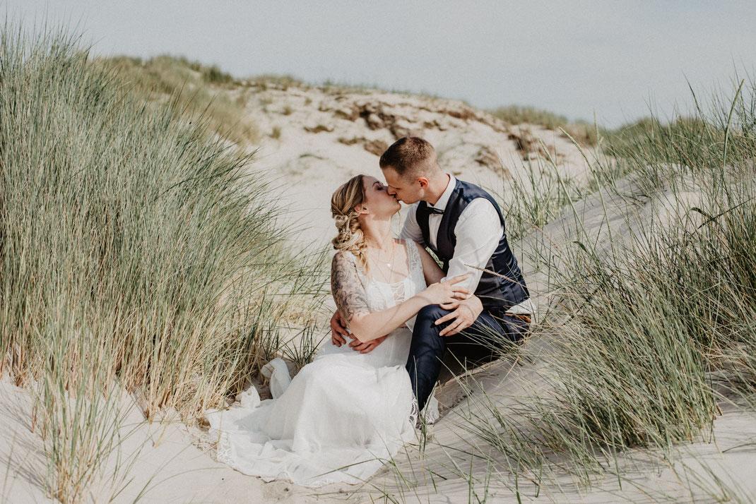 Ein Brautpaar sitzt in einer Düne am Strand und küsst sich