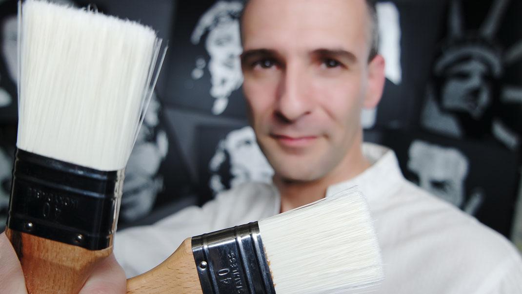 Le peintre erik black avec ses pinceaux dans son atelier d'artiste