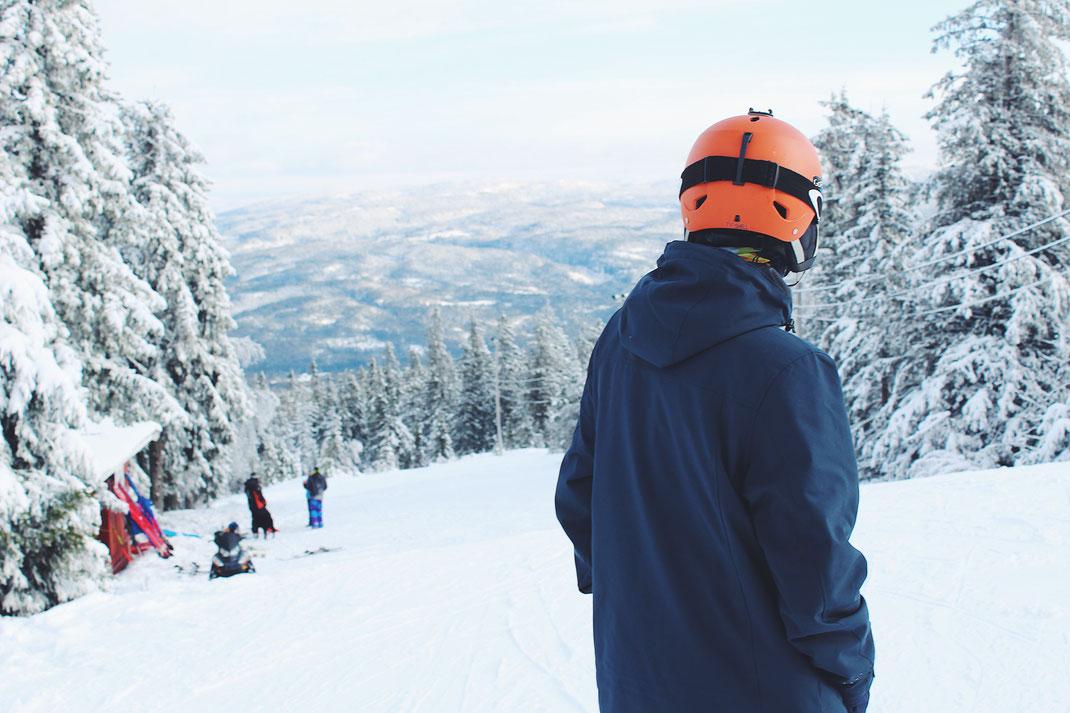 A man in an orange ski helmet enjoying the snow covered view