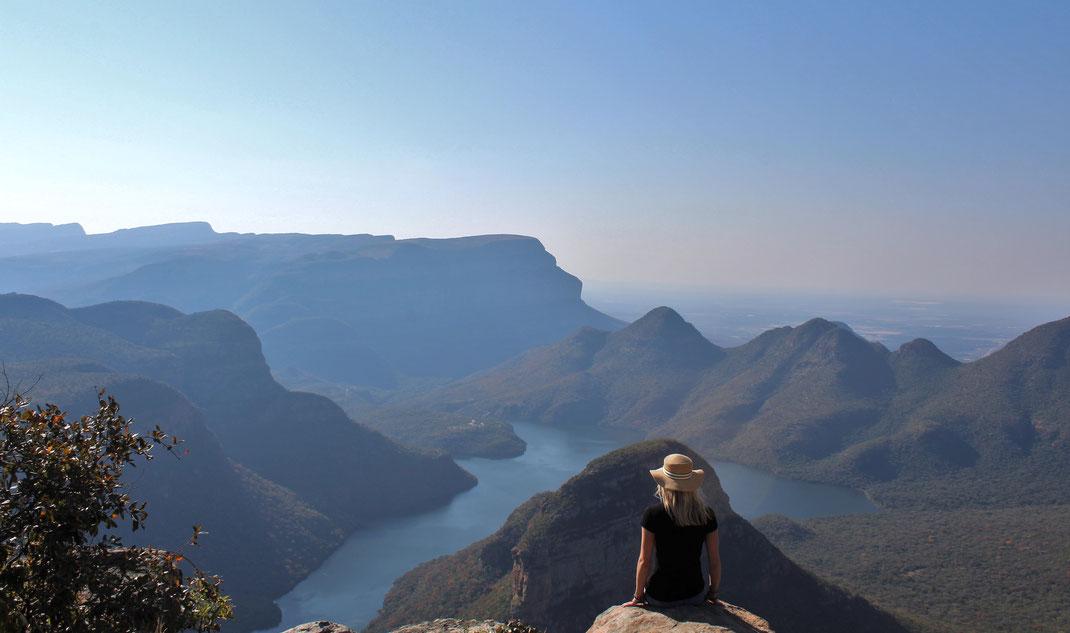 Blonde Frau auf einem Fels in Südafrika, Blick auf einen großen Fluss