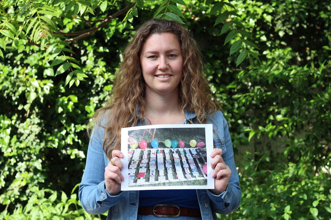 """Die Kulturanthropologin Corinna zeigt ein Foto ihres Projektes """"Veedels-Mosaik"""", das im Bürgerhaus MüTZe beim Bürgerpark Berliner Straße stattfand."""