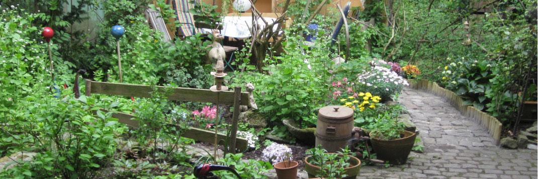 """Gartenansicht Galerie """"Frutti dell'Arte"""" in Aachen im Mai 2015, mit Keramiken, Skulpturen und altem Butterfass, Akelei, Christrose und Margerite in üppigem Grün"""