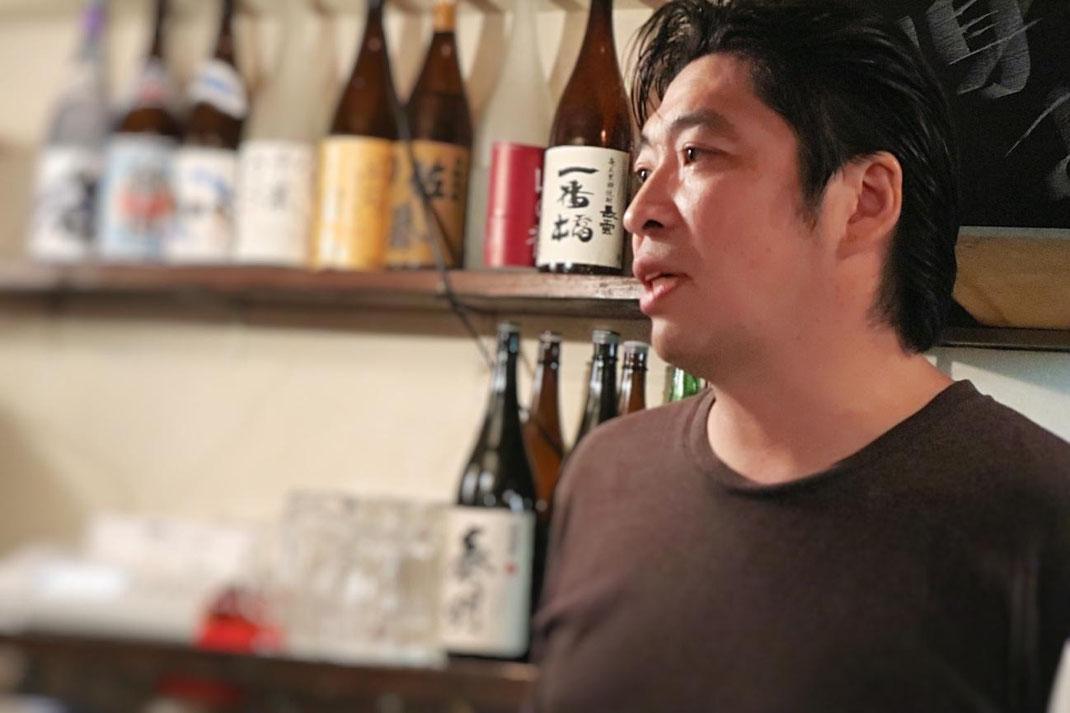 店主の竹見俊一郎さん。お客様と酒器について真剣に話している写真