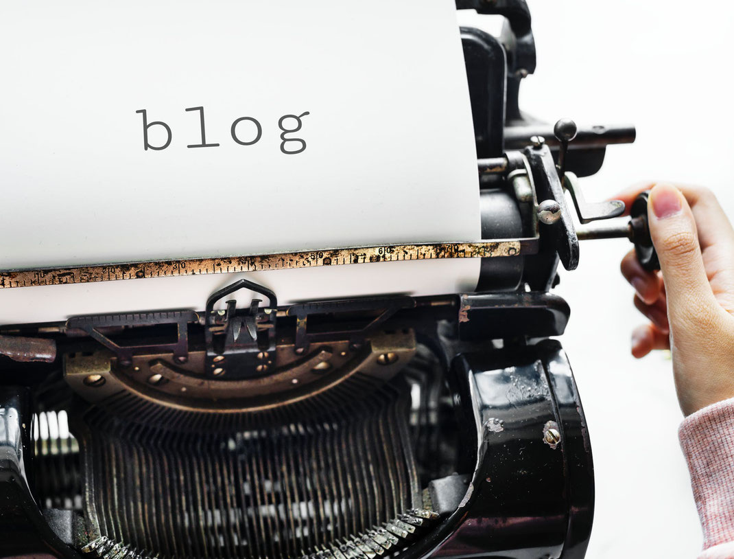 """Eine Schreibmaschine. Auf dem eingelegten Blatt steht das Wort """"Blog"""""""