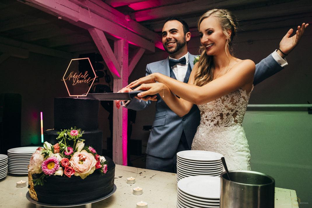 Glückliches Brautpaar beim Torte anschneiden