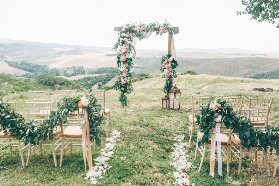 Traubogen und Traustühle mit Blumendeko bei einer freien Trauung in den Weinbergen der Pfalz