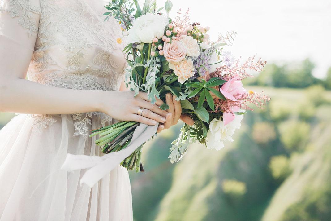 Braut wartet mit ihrem Brautstrauss vor dem Beginn ihrer freien Trauung im Boholook