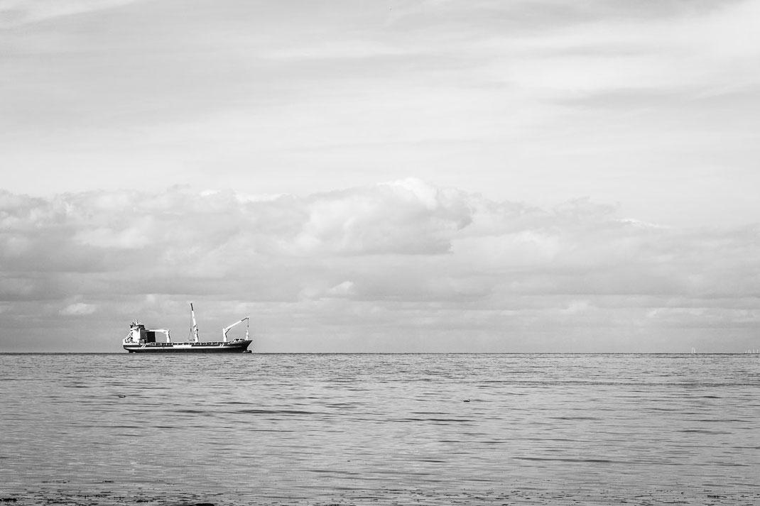 Schiff am Horizont auf einem Ruhigen Meer unter Wolkenhimmel.