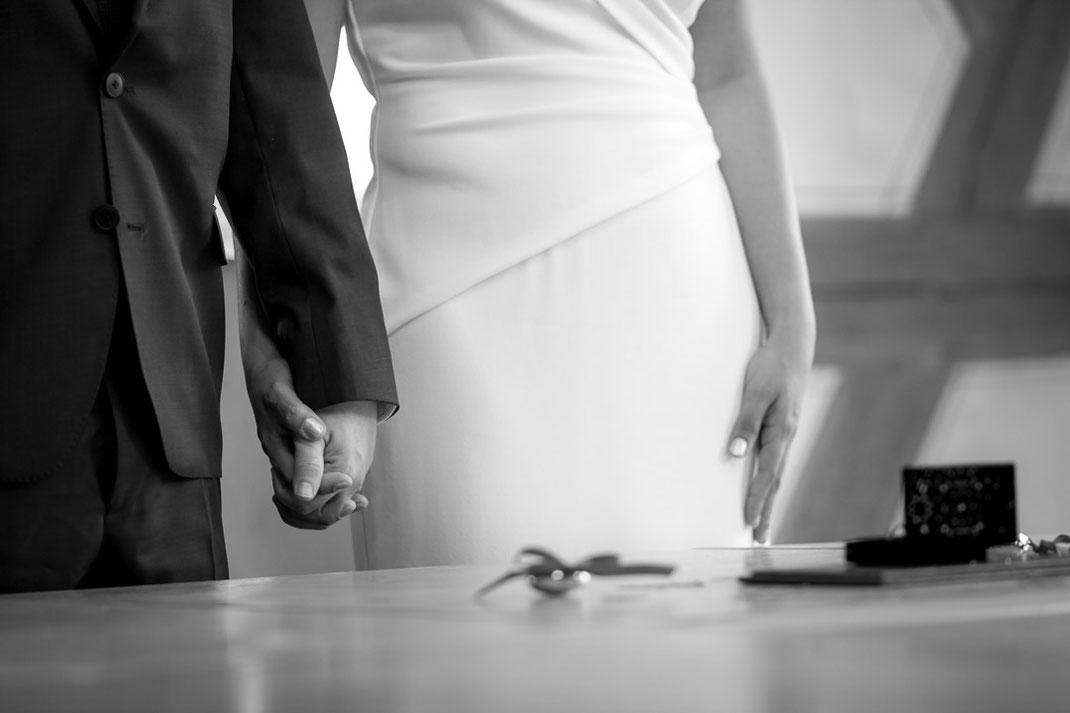 Bild eines Brautpaares das sich vor dem Altar die Hände hält