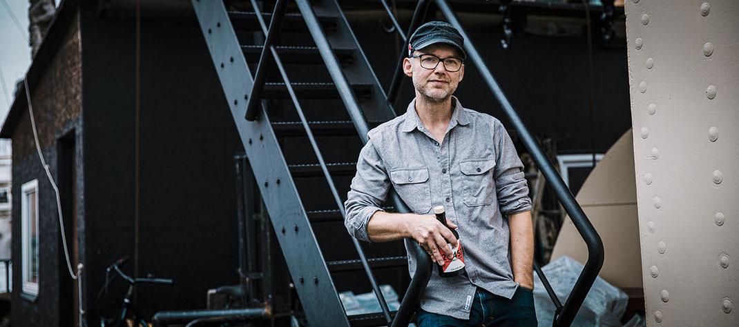 Gründer René Wolf mit 'ner Pulle Hafencity Gin auf dem Hafenkran im Traditionsschiffshafen