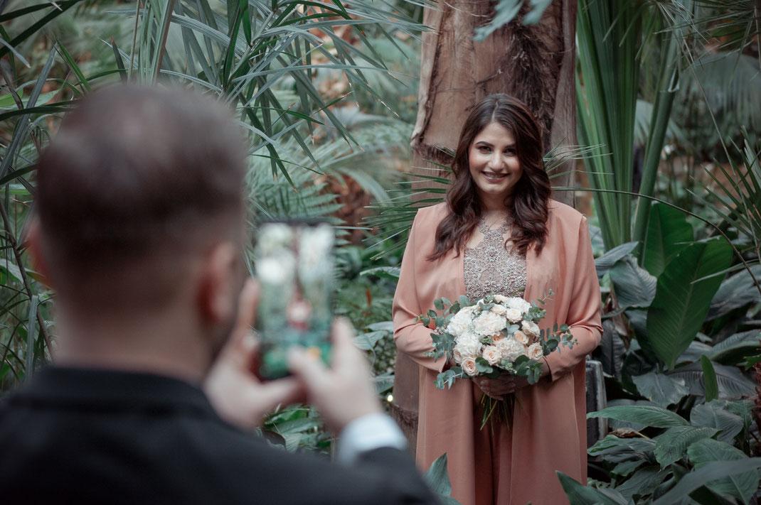 Erstellen Sie nachgestellte Szenarien mit Hilfe von herkömmlichen Mitteln. Lassen Sie es so aussehen, als würde der Mann seine Frau fotografieren wollen.