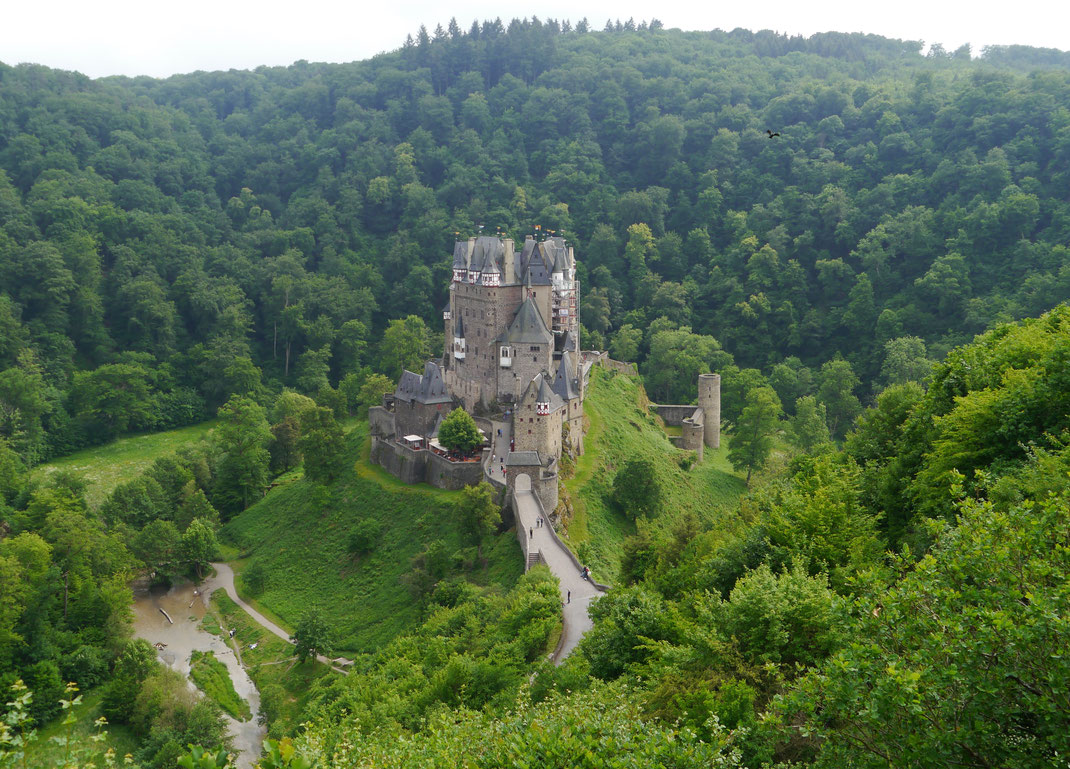 Burg Eltz, umflossen vom Elzbach, auf einem 70 m hohen Felssporn in einem Nebental der Mosel stehend