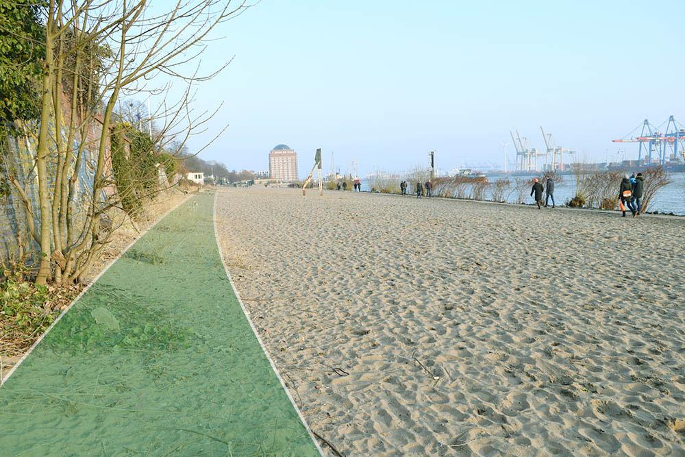 Der leere Strand in Övelgönne an einem sonnigen Wintertag, einige Menschen flanieren auf dem Betonweg neben den Schlackesteinen