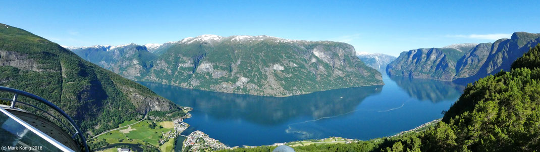 Panorama photo from a 600 meter high platform over snow-topped mountains directly located at mirroring surface of Aurlandsfjord