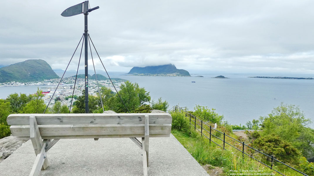 Phot with a white park bench offering a view of town and bay of Ålesund